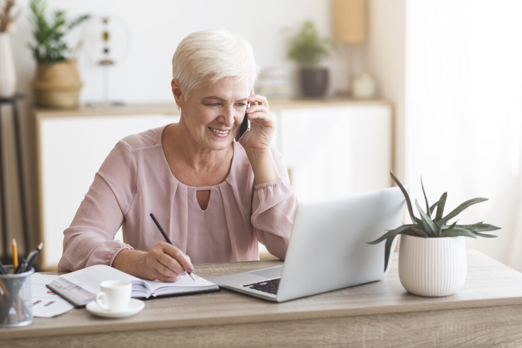 Senior business woman working from home, discussing project with client, making notes in front of laptop, panorama with empty space